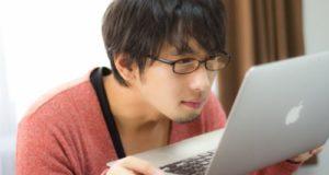 ノートパソコンを持ち上げて画面を見つめる男性