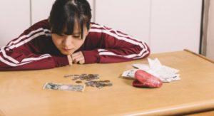 お金を見つめる悲しい表情のジャージの少女
