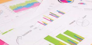 グラフなどの資料が机の上に置かれている画像