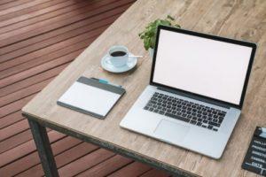 机の上にパソコンやコーヒなどがある写真