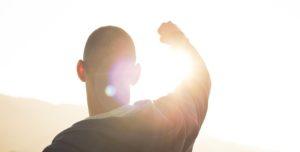 太陽に向かってガッツポーズをしている男性